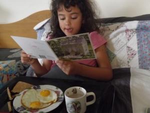 Geralmente o cafe da manha do aniversariante eh escolhido por eles. Ela escolheu, 2 ovos fritos, pão  e chocolate quente. Aqui ela lendo o cartão que a mamãe e papai deu pra ela.